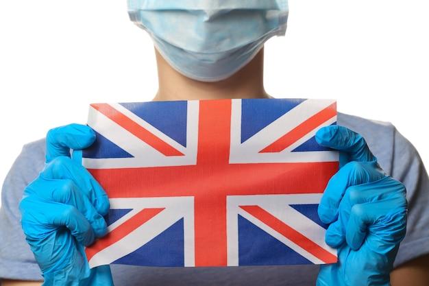 Tema covid-19 pandêmico. mulher em luvas de proteção, máscara facial médica detém a bandeira britânica isolada no branco.
