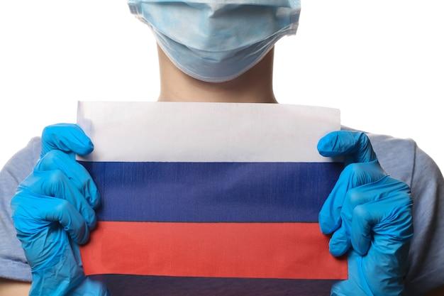 Tema covid-19 pandêmico. mulher em luvas de proteção, máscara facial médica segura a bandeira da rússia isolada no branco.