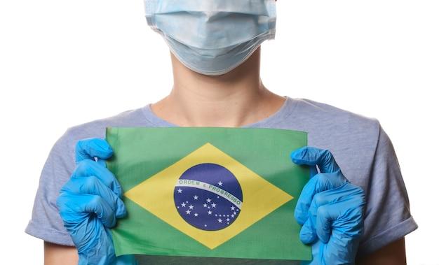 Tema covid-19 pandêmico. mulher em luvas de proteção, máscara facial médica segura a bandeira do brasil isolada no branco.