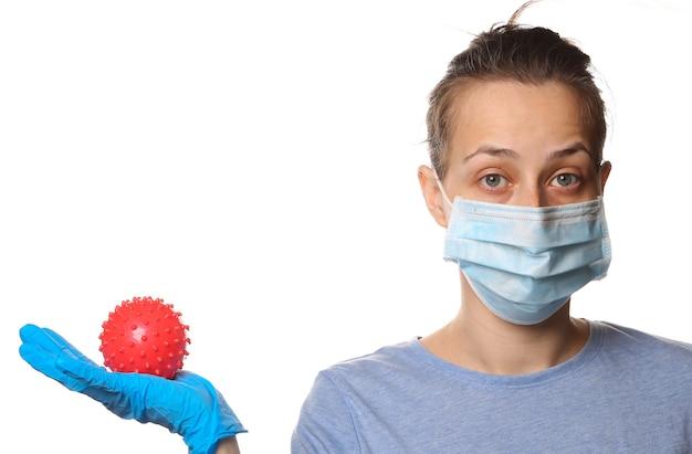 Tema covid-19 pandêmico. mulher em luvas de proteção, máscara médica contém um modelo de cepa de vírus isolado no branco.