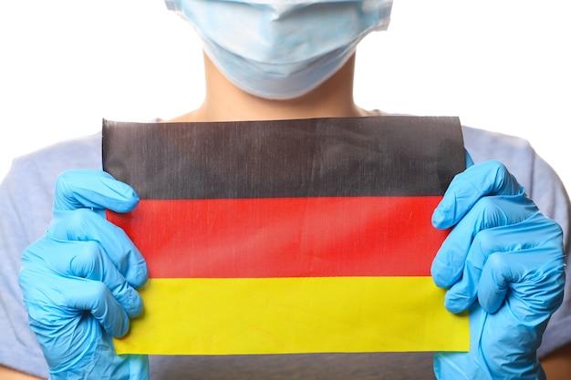 Tema covid-19 pandêmico. mulher em luvas de proteção, máscara médica detém a bandeira da alemanha isolada no branco.