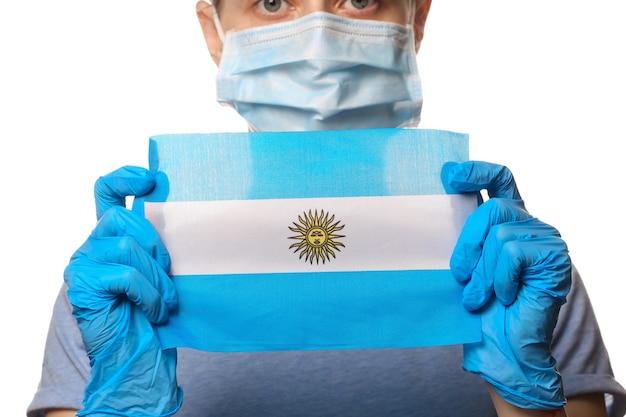 Tema covid-19 pandêmico. mulher em luvas de proteção, máscara médica detém a bandeira da argentina isolada no branco.