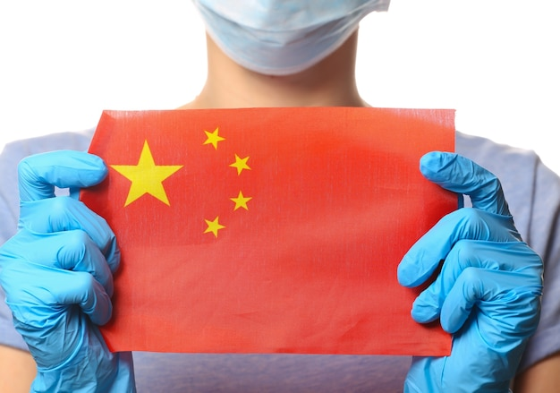 Tema covid-19 pandêmico. mulher em luvas de proteção, máscara médica detém a bandeira da china isolada no branco.