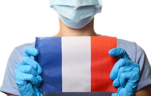 Tema covid-19 pandêmico. mulher em luvas de proteção, máscara médica detém a bandeira da frança isolada no branco.