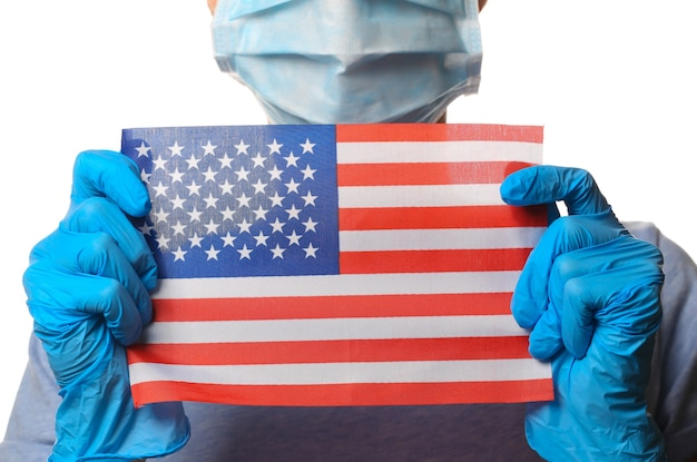 Tema covid-19 pandêmico. mulher em luvas de proteção, máscara médica detém a bandeira dos eua isolada no branco.