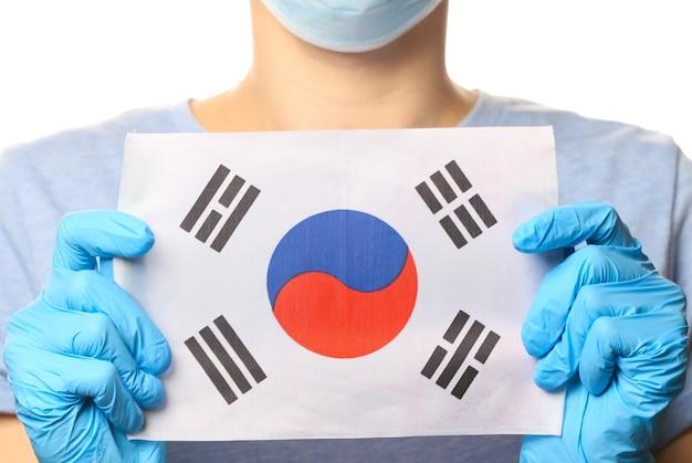 Tema covid-19 pandêmico. mulher em luvas de proteção, máscara médica mantém a bandeira da coreia isolada no branco.