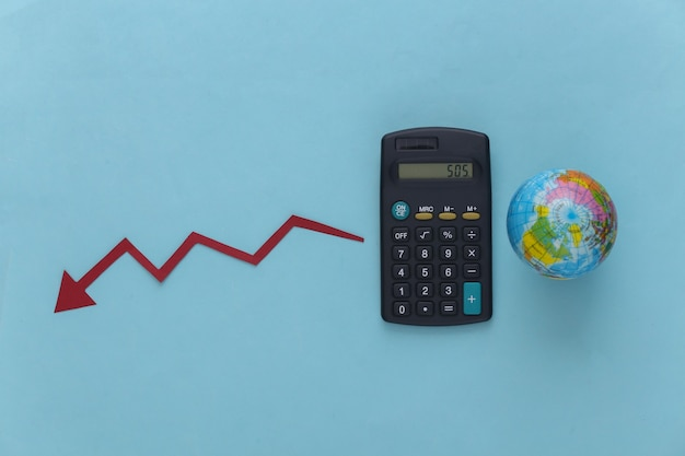 Tema da crise global. calculadora com um globo, flecha caindo tendendo para baixo no azul