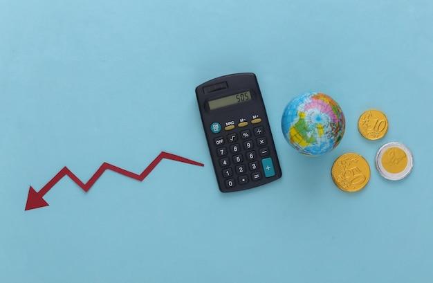 Tema da crise global. calculadora com um globo, moedas, flecha caindo tendendo para baixo no azul