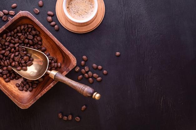 Tema de café. xícara de café quente e prato com grãos de café na mesa de madeira preta.