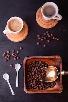 Tema de café. xícaras de café quentes e prato com grãos de café na mesa de madeira preta.