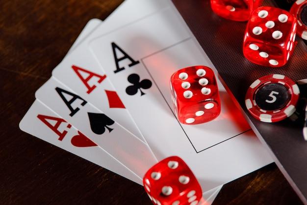Tema de casino online vermelho jogando fichas e cartas de jogos de dados em uma mesa de madeira