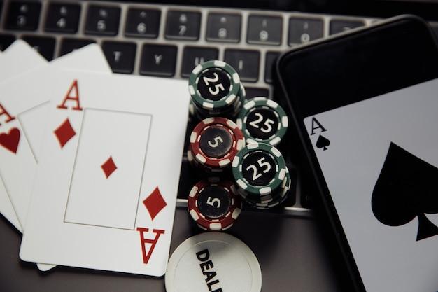 Tema de cassino de pôquer online. fichas de jogo de close-up, smartphone e cartas de jogar no teclado
