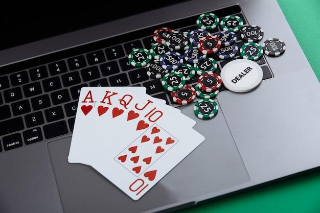 Tema de cassino de pôquer online. fichas de jogo e cartas de jogar no laptop.