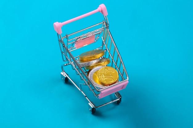 Tema de compras. carrinho de mini-supermercado com moedas em azul