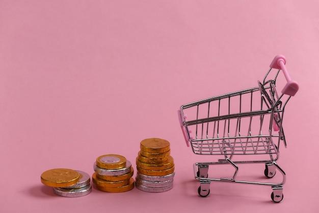 Tema de compras. carrinho de mini supermercado com moedas em rosa.