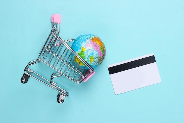 Tema de compras. carrinho de supermercado com globo, cartão de crédito em uma superfície azul. vista do topo