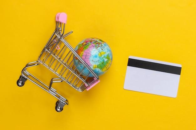 Tema de compras. carrinho de supermercado com globo, cartão de crédito na superfície amarela. vista do topo