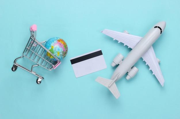 Tema de compras, entrega aérea. carrinho de supermercado com globo, cartão de crédito, avião sobre uma superfície azul. vista do topo