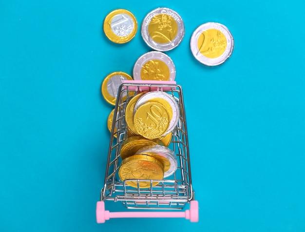 Tema de compras. mini carrinho de supermercado com moedas em bue.