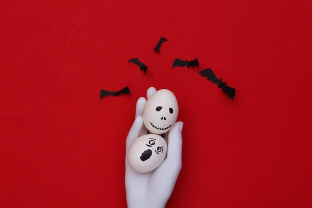 Tema de halloween. mão de manequim segurando ovos com a mão desenhada rosto de fantasma assustador e morcegos em fundo vermelho