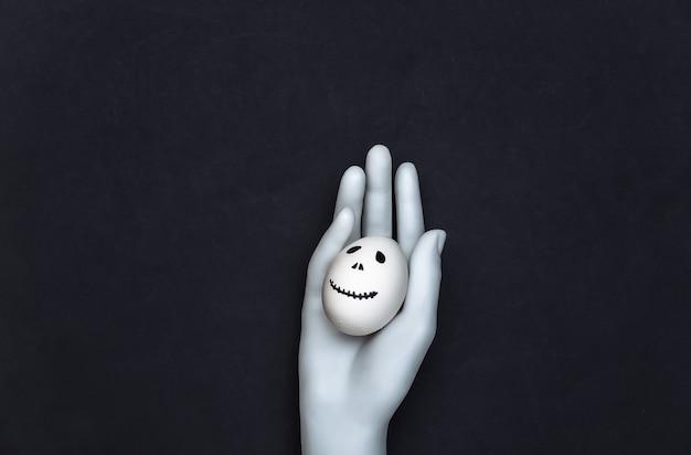 Tema de halloween. mão de manequim segurando um ovo com a mão desenhada rosto de fantasma assustador em fundo preto
