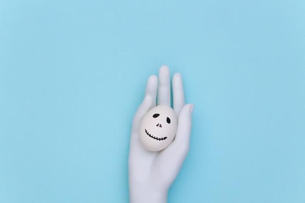 Tema de halloween. mão de manequim segurando um ovo com a mão desenhada rosto de fantasma assustador sobre fundo azul