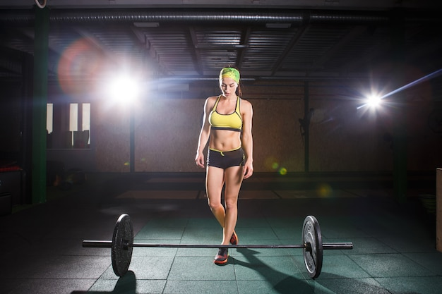 Tema de musculação e treinamento para o corpo bonito, fitness. uma garota forte vai fazer um exercício com barra