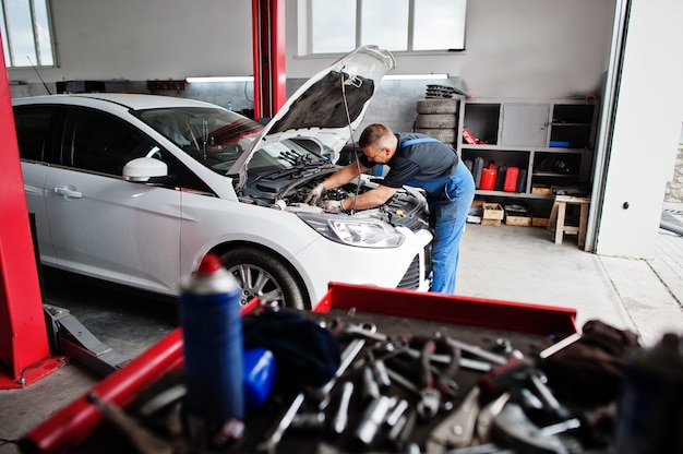 Tema de reparo e manutenção do carro. mecânico de uniforme trabalhando no serviço de automóveis, verificando o motor.