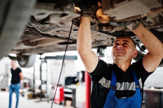 Tema de reparo e manutenção do carro. mecânico de uniforme trabalhando no serviço de automóveis.