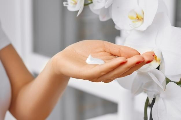 Tema de saúde e cuidados com o corpo linda mão feminina com creme branco em uma sala ensolarada com flores de orquídeas brancas
