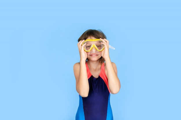 Tema do feriado: menina criança com equipamento de mergulho ou snorkel em uma parede azul. conceito de aventura e descanso