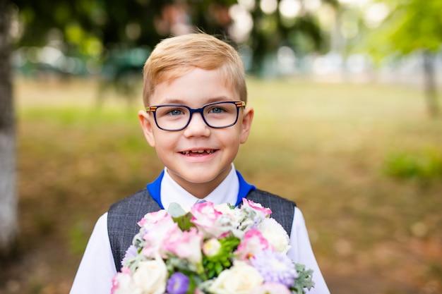 Tema educacional: retrato de um estudante com grandes óculos escuros e gravata azul. quintal da escola, início das aulas