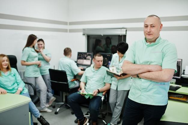 Tema médico. retrato de médico com prancheta contra grupo de médicos reunidos no escritório de ressonância magnética no centro de diagnóstico no hospital.