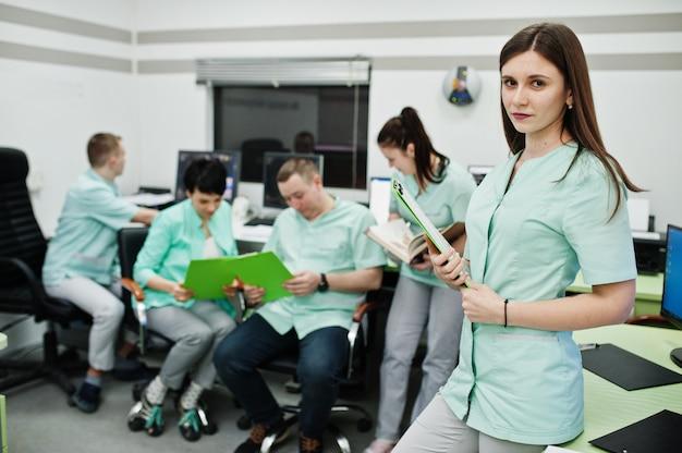 Tema médico. retrato de uma médica com prancheta contra um grupo de médicos reunidos no escritório de ressonância magnética no centro de diagnóstico no hospital.