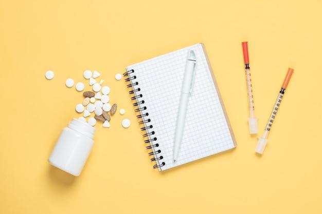 Tema médico. seringas e caderno, comprimidos em um fundo amarelo. vista do topo