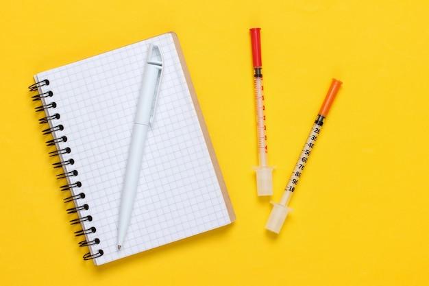 Tema médico. seringas e caderno em um fundo amarelo. vista do topo