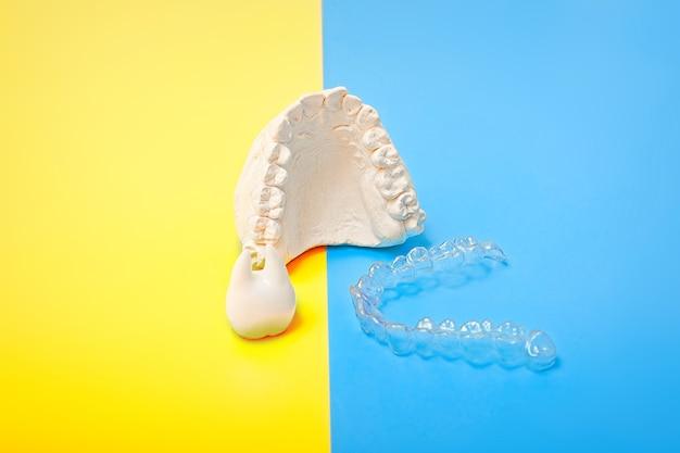 Tema odontológico ortodôntico em fundo azul e amarelo. alinhadores ou aparelho dentário invisível transparente para tratamento dentário