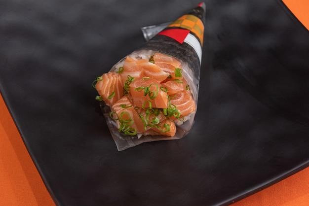 Temaki delicioso e bonito na mesa laranja