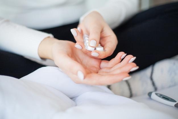 Temperatura alta. close-up mulher doente segurar em sua pílula de mão
