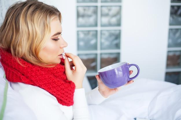 Temperatura alta. jovem mulher olhando para o termômetro, segurando-o nas mãos e deitada na cama