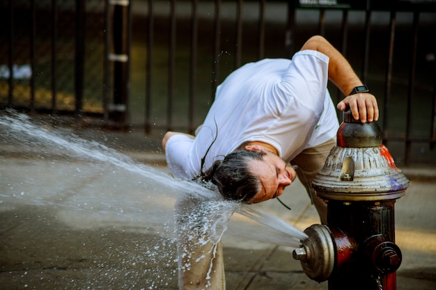 Temperatura de calor forte o homem é refrescado com água de um hidrante