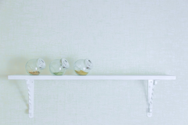 Tempero em garrafas na prateleira de madeira branca. copyspace.