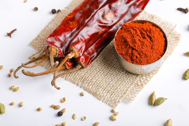 Tempero indiano pimenta vermelha em pó na tigela na mesa branca