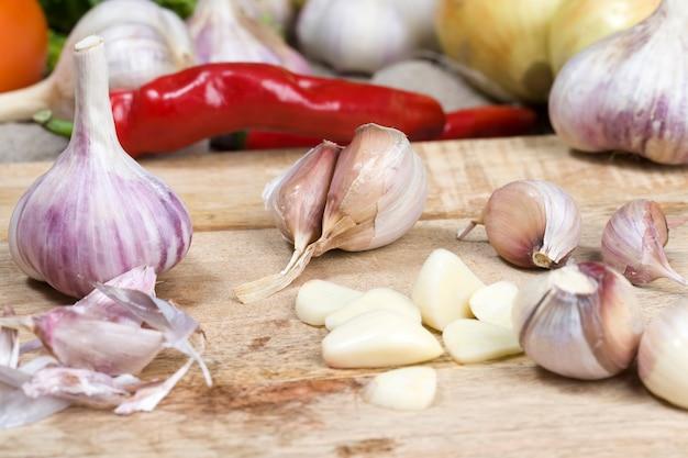 Temperos de alho na mesa da cozinha, cozinhar e saladas de vegetais naturais e frescos, vegetais não são todos lavados e limpos da sujeira, detalhes de alho picante e azedo
