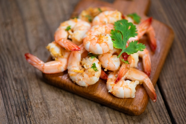 Temperos deliciosos do tempero do camarão no fundo de madeira da placa de corte. camarão cozido ou camarão frutos do mar egoísta