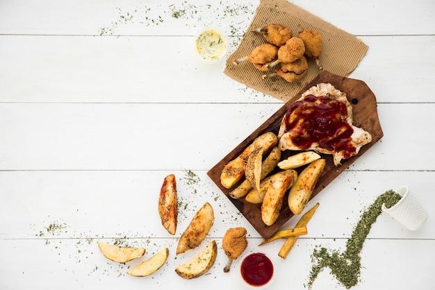 Temperos em torno de carne frita e batatas