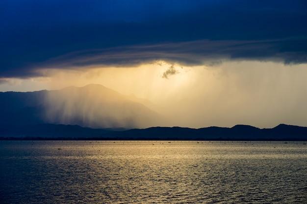 Tempestade de chuva bonita no lago, com céu azul escuro e iluminação penetram do sol