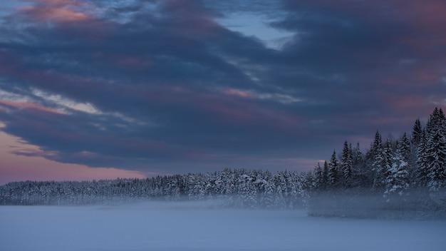 Tempestade de neve de inverno sobre o lago perto da floresta no inverno ao pôr do sol