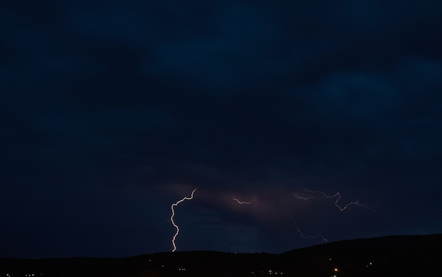 Tempestade de relâmpagos no céu de nuvem escura iluminada pelo brilho de um relâmpago, fenômeno natural