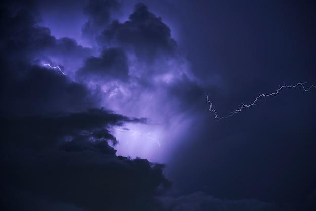 Tempestade do trovão do relâmpago mau tempo, céu azul e nuvem escura.